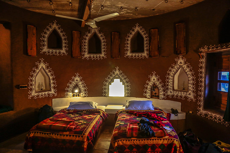 An exquisite interior of a mud house adorned with distinct patterns in white at Desert Resort.